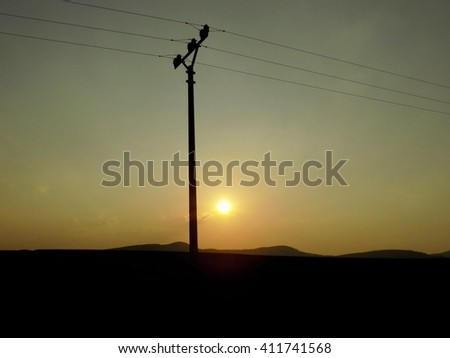 Power line column and sunset - stock photo