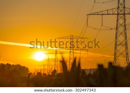Power line in a yellow sky at sunrise in summer