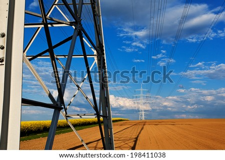 Power line system over clouded blue sky - stock photo