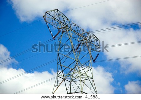 Power line tower against a clean blue cloudy sky.