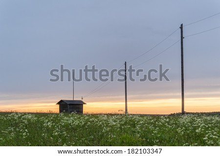Power line with wooden poles and barn against sunset background.