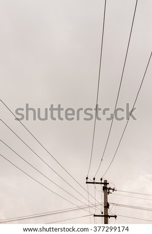 Power lines against cloudy sky - Power transmission lines from a transmission pole run across the sky covered with dark grey rain clouds.