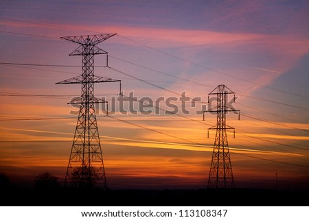 Power Lines And Electrical Towers In Silhouette Against A Vibrant Sunset Sky, Northern Ohio, USA