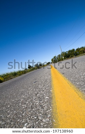 Power lines and fencing line the blacktop of the road leading off into the distance. - stock photo