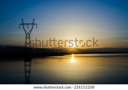 Power lines and lake water at sunset with a bright yellow sun shining rays over the mountains and water suited for a wallpaper background with a blue cloudy sky and lots of electricity pillars - stock photo