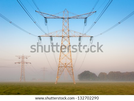 Power lines and pylons in ground fog; it's early in the morning. - stock photo