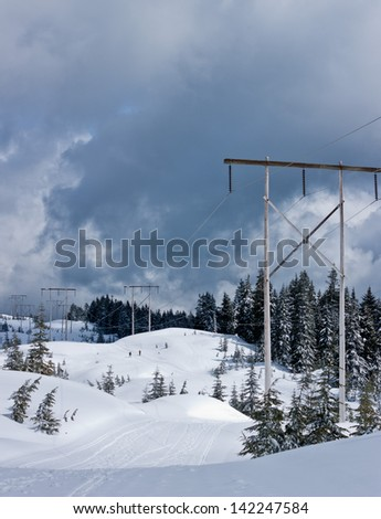 power lines crossing the top of a mountain - stock photo