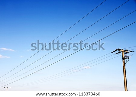 Power lines in front of a blue sky. - stock photo