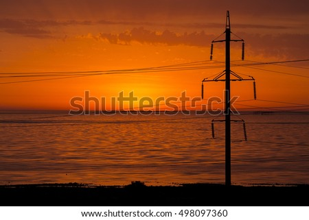 Power lines near the sea in a background of red sunrise light