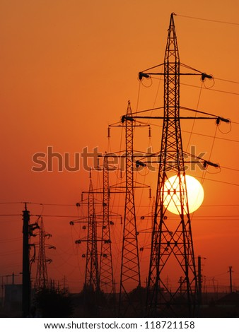 Power lines poles over setting sun - stock photo