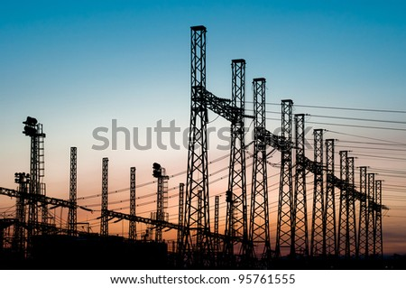 Power lines row silhouettes in the city center at the sunset - stock photo