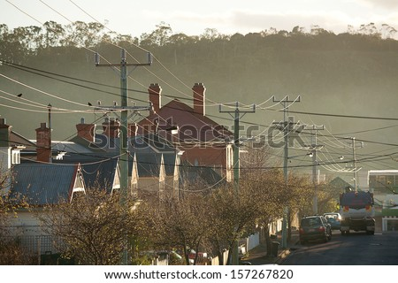 Power Lines running through a suburban street beautifully backlit by the early morning sun - stock photo