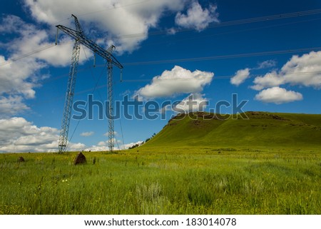 Power lines. Sky clouds and landscape with hills meadow