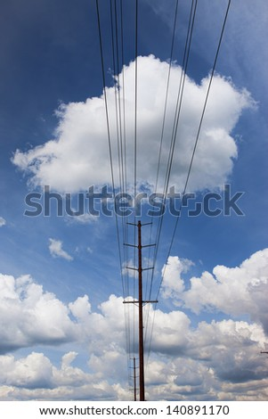 Power lines under a bright blue sky filled with puffy white clouds.