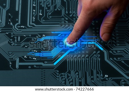 power mans finger is charging passive circuit board with blue energy