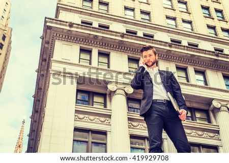Power of Technology in daily life. Dressing in black suit, American Businessman with beard standing outside vintage office building in New York, arm carrying laptop computer, talking on cell phone. - stock photo