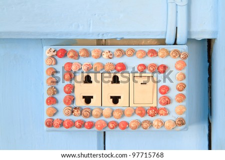 power outlet and light switch decoration with sea shell - stock photo