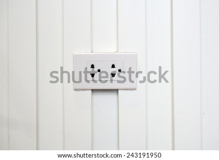 Power outlet on white wall background - stock photo