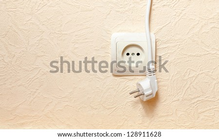 power outlet with plugged in cord closeup on beige. limited dof focus on outlet. - stock photo