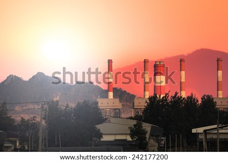 Power plant and electric lines with sunset time and mountain background - stock photo
