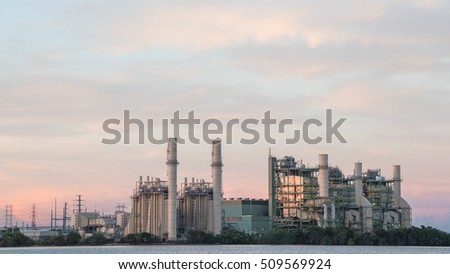 Power plant at industrial park in San Antonio, US. Power station at dusk. The lake or reservoir in front provides cooling pond, recharged with treated wastewater for this power plant. Panorama style.