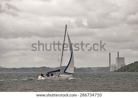 Power plant close to sea and sailboat in hard weather. Littlebelt in Denmark. - stock photo