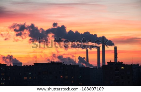 Power Plant emissions seen above residential blocks from a city during sunrise. Environmental pollution. Factory pipe polluting air.