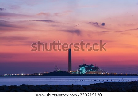 Power plant factory silhouette over sunset - stock photo