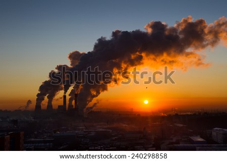 Power plant pipes with swirling smoke at sunrise. Environmental pollution. View against the sun. - stock photo