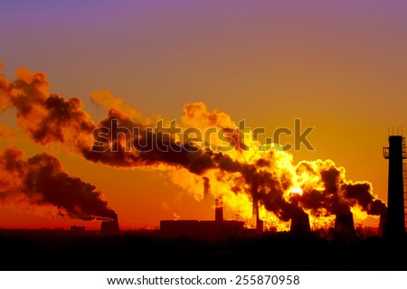 power plant smokestacks at sunset - stock photo