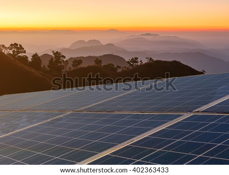 Power plant using renewable solar energy with sunset over mountains background