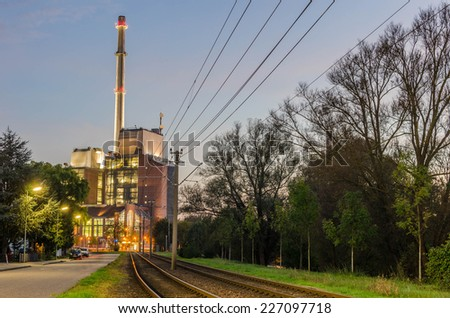 Power plant with a big chimney in front of railroad tracks at sunset - stock photo