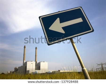 Power plant with arrow sign against cloudy blue sky - stock photo
