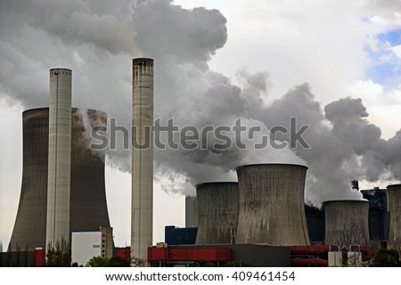 power plant with chimneys and steaming cooling towers, gray clouds rise in the sky, concept for energy industry, co2 emissions and environmental protection - stock photo