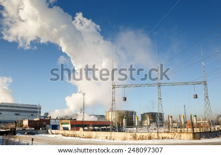 power plant with smoke from stacks in winter