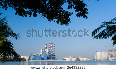 power plant with tree silhouette as it foreground to illustrate go green  - stock photo