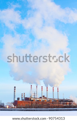 Power plant with white smoke over blue sky - stock photo