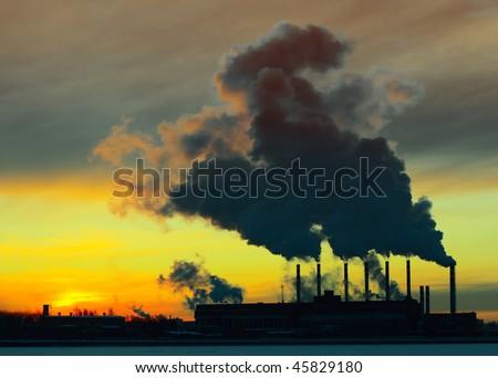 Power plant with yellow smoke - stock photo