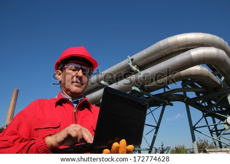 Power Plant Worker With Notebook Computer. Industrial worker with notebook working in a power plant. An engineer in red overalls and hard hat against pipelines. - stock photo
