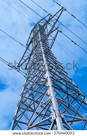 Power pole with high voltage against the blue sky