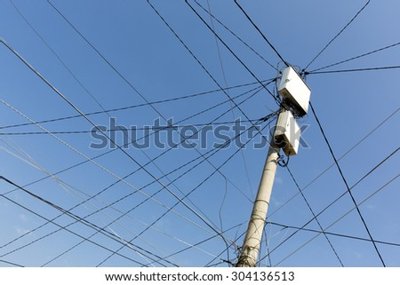 Power pole with white boxes with many electric cables in gypsy neighborhood in Sofia, Bulgaria.