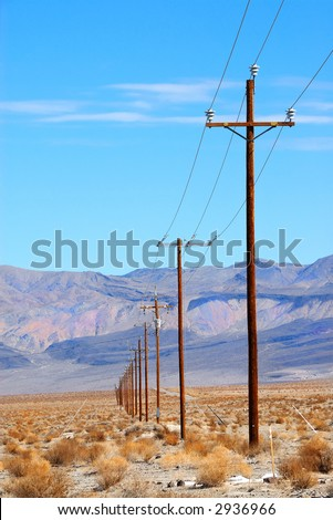 Power poles lined up in the desert of Death Valley, California, USA against a  backdrop of mountain ranges.