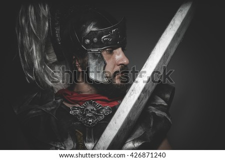 Power, Praetorian Roman legionary and red cloak, armor and sword in war attitude - stock photo