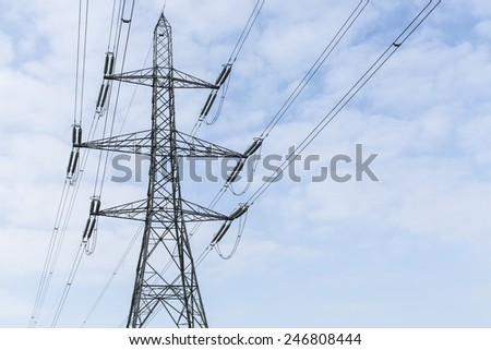 Power pylon alone against the light blue sky with clouds - stock photo