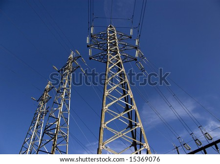 Power pylons against a deep blue sky.