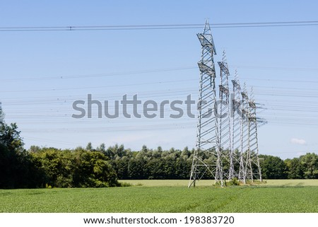 Power pylons and high voltage lines in an agricultural landscape with a blue sky on a sunny day in the summer season. - stock photo