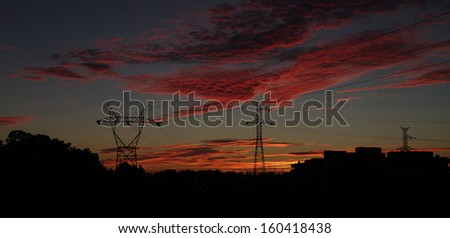 Power pylons over a fantastic sunset sky.(Panoramic picture,not a crop) - stock photo