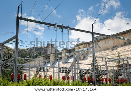 Power station with dam at background in nature environment. - stock photo