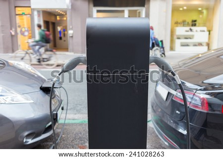 Power supply for electric car charging.  Electric cars charging station. Power supply plugged into an electric car being charged.