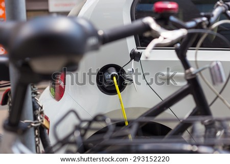 Power supply for electric car charging.  Urban electric car charging station on a busy street. Close up of the power supply plugged into an electric car being charged. - stock photo